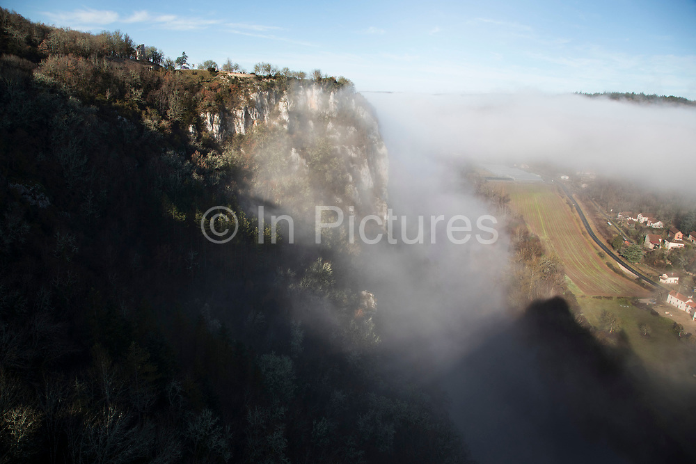 Morning fog and mist in St Cirq-Lapopie, France. Saint-Cirq-Lapopie is a commune in the Lot department in south-western France. It is a member of the Les Plus Beaux Villages de France The most beautiful villages of France association. Its position, originally selected for defense, perched on a steep cliff 100 m above the river has helped make the town one of the most popular tourist destinations in the department.