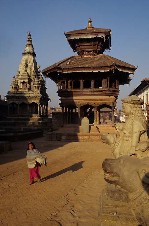 Asia, Nepal, Kathmandu Valley, Bhaktapur. Girl walks through Durbar Square; Hindu Vatsala Durga & Chyasilin Temples.