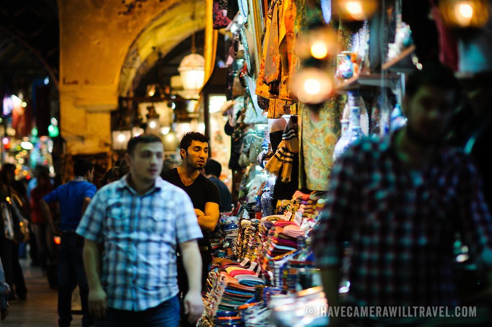 A shopkeeper sellings silk scarves inside Istanbul's historic Grand Bazaar. Narrow depth of field.