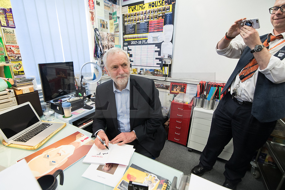 © Licensed to London News Pictures . 22/03/2018. Manchester, UK. JEREMY CORBYN signs a copy of the Labour Party manifesto during a visit to a class at Stretford High School in Trafford , after launching of the Labour Party's local election campaign . Photo credit: Joel Goodman/LNP