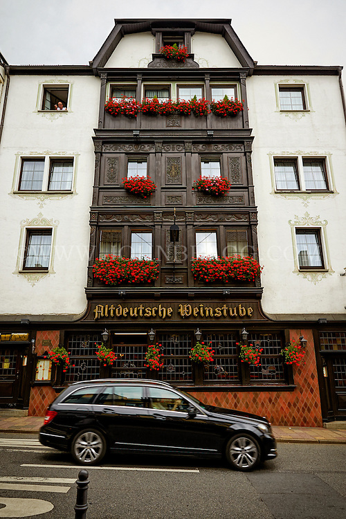 View outside of the Altdeutsche Weinstube Hotel and Restaurant, tourists peeking out the window, and a black car driving past, Rüdesheim, Germany (Vertical).