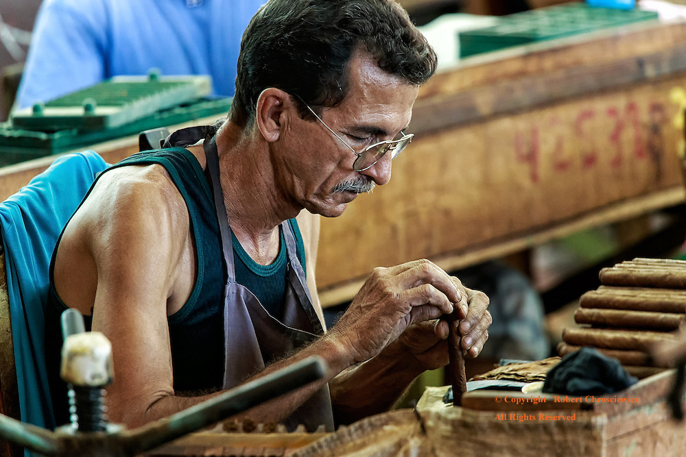 Hand Rolled: A man demonstrates his life time skill and manual dexterity as he expertly hand rolls another cigar at the factory in Trinidad Cuba.