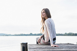 Young woman loneliness sitting jetty thoughtful