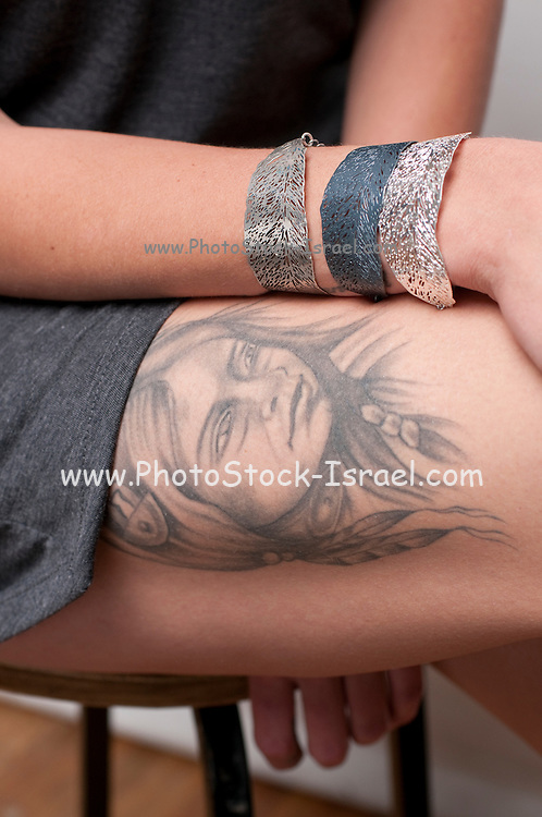 A hip and trendy young woman with a tattoo of a squaw on her thigh Model release available