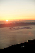Sun rises behind Sao Jorge island. From the summit of Pico mountain the central islands of the archipelago can be seen. At the distance Terceira island is also observed. Pico is the highest portuguese mountain with 2351m high