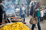People walk past a stall selling paella and sausages. Borough Market is a thriving Farmers market near London Bridge. Saturday is the busiest day.
