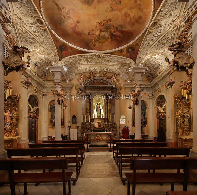 Chapel of Our Lady of El Carmen, with painted ceiling, altarpiece dedicated to the Virgin and sculptures of angels on the columns, 18th century, Hospital de Mujeres (Women hospital), a hospital for destitute women and now the seat of the Bishopric of Cadiz, in Cadiz, Andalusia, Southern Spain. Cadiz is one of the oldest cities in Europe, founded by the Phoenicians in 1100 BC, and later became a Carthaginian then a Roman city, and Spain's constitution was signed here in 1812. It is situated on a peninsula on the Costa de la Luz. Picture by Manuel Cohen