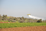Air Tractor AT-802F fire fighting plane (4x-AFY) operated by him-Nir Aviation is dropping flame retardant (here water was used to avoid damage and costs) during a joint forces large scale forest fire exercise in Israel in January