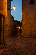 Warm light from an overhead street lamp, illuminates deserted medieval cobbled streets, on 26th May, 2017, in Lagrasse, Languedoc-Rousillon, south of France. Lagrasse is listed as one of France's most beautiful villages and lies on the famous Route 20 wine route in the Basses-Corbieres region dating to the 13th century.