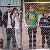 Thoreau High School students lean on a fence to watch their classmates play a baseball game in Thoreau Friday.