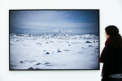 "© Licensed to London News Pictures. 14/03/2019. London, UK. A woman views a photograph of Point Hope, Alaska USA, May 2018. <br /> Carmignac Photojournalism award - ""Arctic - New Frontier"" exhibition by Yuri Kozyrev and Nadir Vab Lohuizen on show at Saatchi Gallery. Yuri Kozyrev and Kadir van Lohuizen (NOOR) were awarded the 9th edition of the Carmignac Photojournalism Award dedicated to the Arctic. The endowment allowed them to carry out their pioneer double polar expedition 'Arctic: New Frontier'. <br /> The exhibition runs from 15 March, it will run until 5 May 2019 at Saatchi Gallery. Photo credit: Dinendra Haria/LNP"