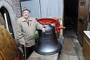 """UK, November 24 2014:  Brian Horrell stands next to the new tenor bell that will be installed at All Saints East Budleigh church. The inscription on the bell states """"Anne and Brian Horrell married at All Saints East Budleigh 6th June 1959"""" . Copyright 2014 Peter Horrell."""