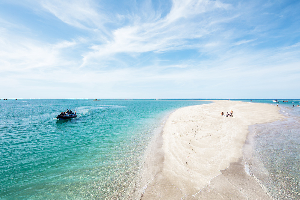 People enjoying the stunning white sand and crystal clear calm, water at the tropical paradise of the Minquiers, off the coast of Jersey, CI