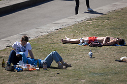 © Licensed to London News Pictures. 23/04/2021. London, UK. A man sunbathes as members of the public relax and enjoy the sunny weather in Potters Fields Park in central London. Temperatures are expected to rise with highs of 16 degrees forecasted for parts of London and South East England today . Photo credit: George Cracknell Wright/LNP