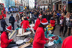 "London, December 23rd 2014. Dubbed by retailers as the ""Golden Hour"" thousands of shoppers use their lunch hour to do some last minute Christmas shopping in London's West End. PICTURED: A steel band plays Christmasd songs outside Bond Street station."