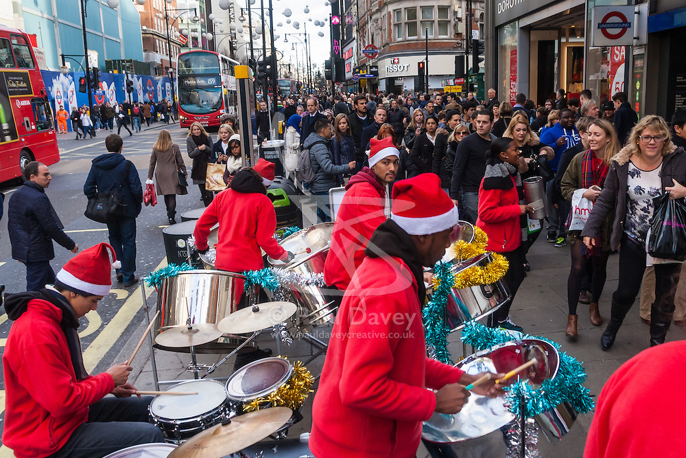 """London, December 23rd 2014. Dubbed by retailers as the """"Golden Hour"""" thousands of shoppers use their lunch hour to do some last minute Christmas shopping in London's West End. PICTURED: A steel band plays Christmasd songs outside Bond Street station."""