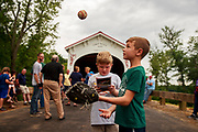 """Eric Peden, 7-years-old, tosses a baseball as community members  gather before the ribbon cutting at the Cedar Ford Covered Bridge crossing Beanblossom Creek on Old Maple Grove Road at """"Millikan's Ford,"""" Sunday, June 9, 2019 in Washington, Indiana Township."""