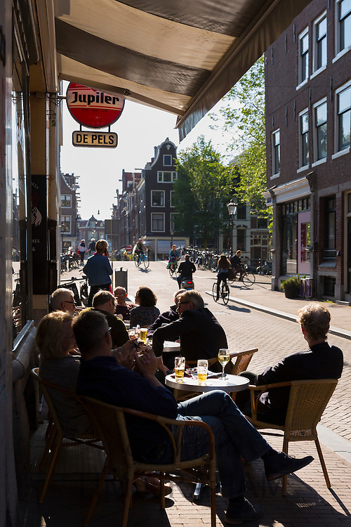 Local people drinking at bar corner of Elandsgracht and Prinsengracht in Jordaan district of Amsterdam, Holland
