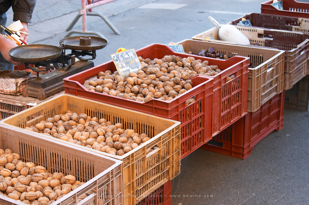 Walnuts and dried plums for sale at a market stall at the market in Bergerac. a very oldfashioned scale Bergerac Dordogne France