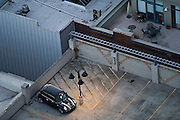 A small car is parked on the lit roof of a tall parking garage in downtown Seattle, Washington.