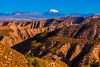 Badlands near Castillejar in the Altiplano of Granada Province (with snowcapped La Sagra peak in background), Andalusia, Spain.