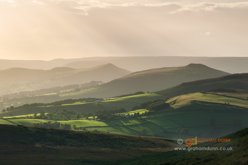 Evening light on fields below WIn Hill & Lose Hill in the Peak District. Kinder Scout forms the horizon in this classic scene, as captured from below Stanage Edge. Derbyshire, England, UK.