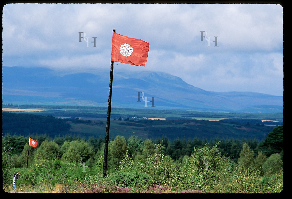 Visitors stop beside red flags marking battle lines of Jacobite Highlanders at Culloden Moor on April 16, 1746; Inverness, Scotland.