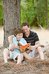 Man and boy enjoying a book together outdoors