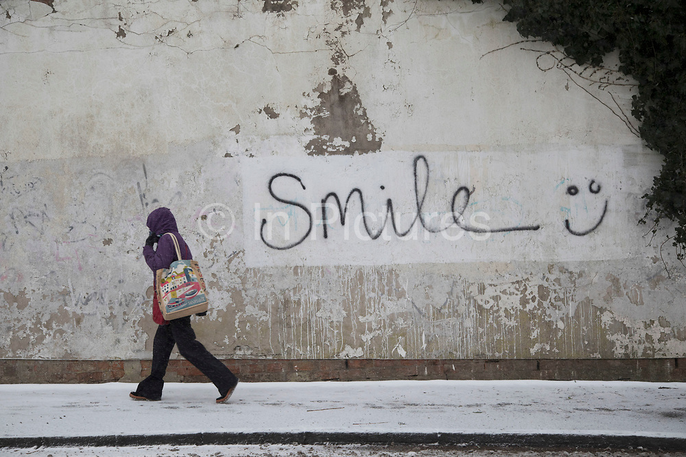 Smile graffiti during freezing weather, dubbed The Beast from the East due to the sub zero cold temperature winds coming in from Siberia, descends on Kings Heath High Street on 1st March 2018 in Birmingham, United Kingdom.