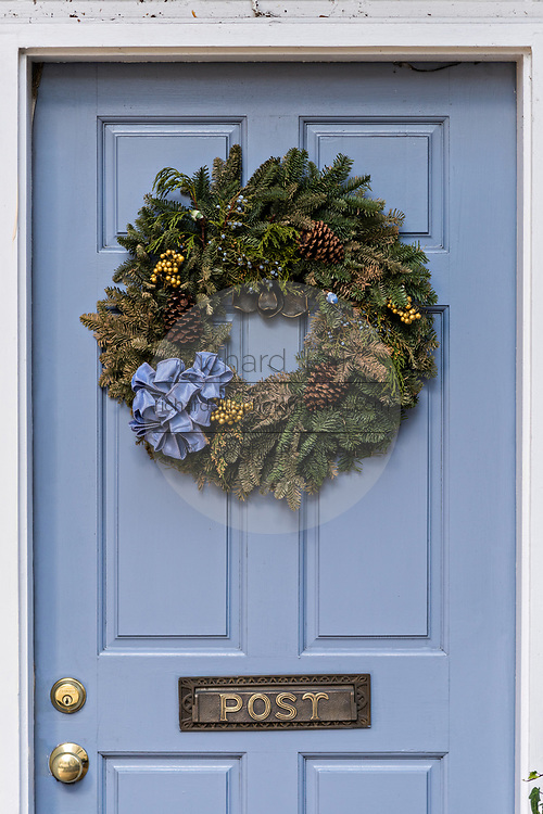 A blue wooden door of a historic home decorated with a Christmas wreath on Tradd Street in Charleston, SC.