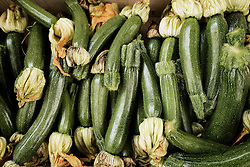 Heap of green courgettes for sale at market, Puglia, Italy