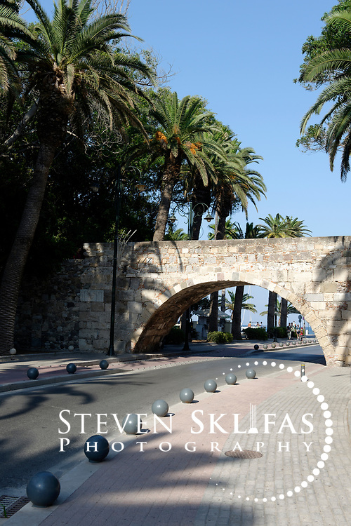 Kos Town. View of Palm Tree Avenue and the stone arched bridge that connects the castle to the Hippocrates square. The Avenue was once the castle moat. Kos is part of the Dodecanese island group and birthplace of the ancient physician and father of medicine, Hippocrates.