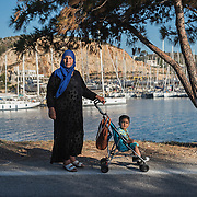 Syrian-Kurd refugee Shaaf Yunis, 57, pushing her one year old grandson, Leven Kendi, past a yachting marina.