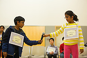 Rishik Gandhasri, left, takes the microphone from Nandana Kurup during the fourth through sixth grade segment of the 2016 Milpitas Youth Spelling Bee at the Milpitas Senior Center in Milpitas, California, on January 22, 2016. (Stan Olszewski/SOSKIphoto)