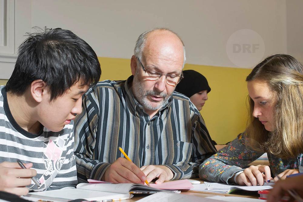Nederland Rotterdam 23-09-2009 20090923 Foto: David Rozing  Serie over onderwijs, het Libanon Lyceum Kralingen,  openbare scholengemeenschap voor mavo, havo en vwo.   Lesuur wiskunde. Een leraar behandelt de leerstof, geeft uitleg aan een groepje leerlingen tijdens het zelfstandig klassikaal werken.  Lesuur wiskunde.   , uitleg, uitleg geven, uitleggen, vaardigheden, vaardigheid, voor de klas staan, voortgezet, vut, writing, young, Youth, zachte sector, zelfstandig werken , , resultaten samenstelling, samen, samenstelling, scholen, scholengemeenschap, scholier, scholieren, scholing, school, schoolbank, schoolbankje, schooljaar, schoolprestaties, schools, schoolse, schoolse situatie, schrift, schriftelijk, schriftelijke, schrijven, senior, senioren, seniors, socialize, socializing, student, students, studeren, studie, studieboek, studies, studieuur, study, studying, teacher, teaching, tekst, the netherlands, toekomst, toelichten, toelichting geven, vinger in de lucht houden, vinger in de lucht steken, vinger opsteken, vragen                                                    .Foto: David Rozing