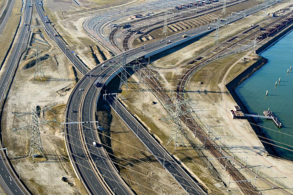Nederland, Zuid-Holland, Rotterdam, 18-02-2015; Euopaweg buigt af naar de Maasvlakte  en Tweede Maasvlakte (MV2). Verder Emplacement Maasvlakte, Distripark en water van de Hartelhaven. Infrabundel van autosnelweg N15, spoorweg (Betuweroute) en hoogspanningsleidingen. <br /> New and man-made land in the North sea <br /> designated for the Port of Rotterdam. Infrastructure bundle: motorway, railway (Betuweroute) and power lines.<br /> luchtfoto (toeslag op standard tarieven);<br /> aerial photo (additional fee required);<br /> copyright foto/photo Siebe Swart