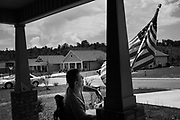 """BIRMINGHAM, AL – JUNE 13, 2015: Matthew Seals, 47, adjusts a flag on the porch of his new home in the Winchester Hills neighborhood. <br /> <br /> In April 1998, a deadly F5 tornado ripped through the suburbs of Birmingham, Alabama, killing 32 people and destroying hundreds of homes. Seventeen years later, Matthew Seals is still learning to cope with the loss of his youngest son, who was killed in the storm. With help from Habitat for Humanity, Seals completed construction on a new home in 2015, where he continues to raise his remaining children and his new life as a paraplegic. Despite his own suffering from the tragedy, Seals volunteers with Habitat to help other families find their own form of stability through home ownership. """"Habitat gives you an opportunity to help yourself,"""" Seals said. """"Not just for the immediate need, but for the long term to become more self-sufficient, more self-confident, and more self-reliant."""""""