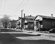 """Y-510222-05. slum area. SW Portland. Street sign at end of block says SW 2nd, house in foreground address is 119. February 22, 1951 (published in Oregonian March 4, 1959 pg. 29. Caption: """"Portland's city planning commission makes clear what is recognized by city planners everywhere – that most blighted areas of the average city once were the best residential districts. For this reason, they say, districts in which older homes like these pictured right , in Portand's southeast district, are ideal as sites for new development programs financed by private investors. Homes like these can be easily removed, thus lowering cost of acquiring sites."""")"""