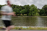 MERTHYR TYDFIL, Wales - 04 JUNE 2020 - A runner in motion blur runs around the lake on his daily exercise