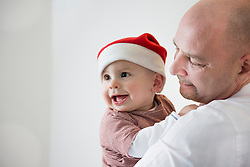 Toddler with Christmas cap in the arms of his father