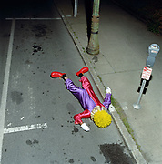 Male clown lying face down on street, elevated view