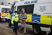 A Metropolitan Police officer arrests an Insulate Britain climate activist who had blocked a M25 slip road at Junction 14 close to Heathrow airport as part of a campaign intended to push the UK government to make significant legislative change to start lowering emissions on 27th September 2021 in Colnbrook, United Kingdom. The activists are demanding that the government immediately promises both to fully fund and ensure the insulation of all social housing in Britain by 2025 and to produce within four months a legally binding national plan to fully fund and ensure the full low-energy and low-carbon whole-house retrofit, with no externalised costs, of all homes in Britain by 2030.