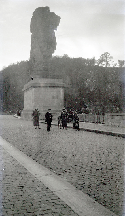 family posing by a very large lion statue 1920s