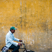 Blurred figure of Vietnamese man riding bicycle past yellow wall