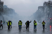 December, 8th, 2018 - Paris, Ile-de-France, France: Demonstrators on Champs Elysees with tear gas smoke. The French 'Gilets Jaunes' demonstrate a fourth day. Their movement was born against French President Macron's high fuel increases. They have been joined en mass by students and trade unionists unhappy with Macron's policies. Nigel Dickinson
