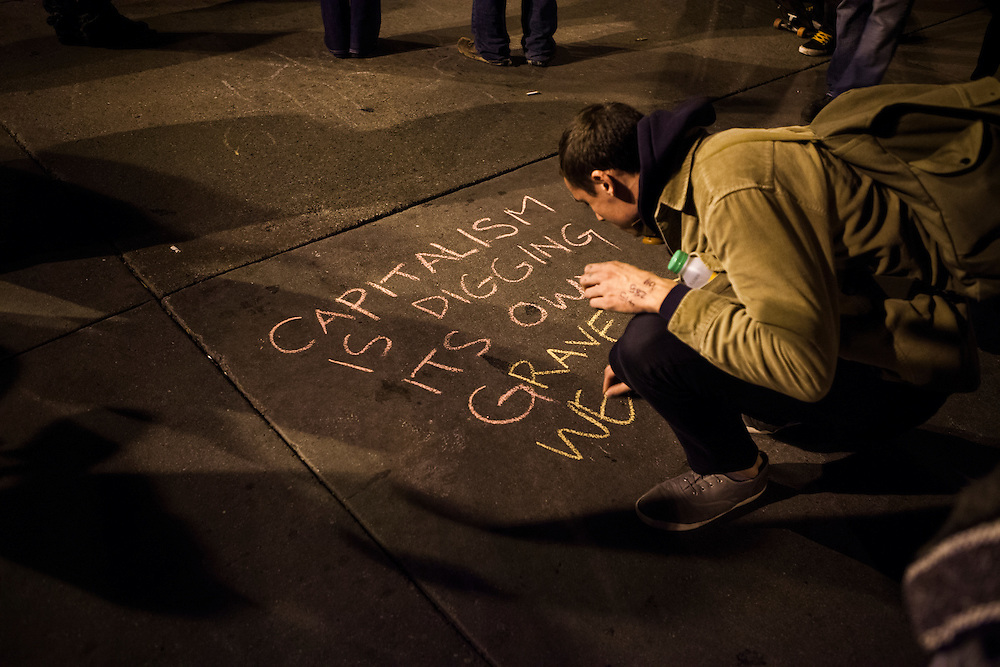 OAKLAND, CA - NOVEMBER 14, 2011: An Occupy Oakland protester scrawls a message on the floor in front of Frank H. Ogawa Plaza.