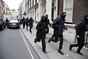 London, UK. Tuesday 11th June 2013. Anti capitalist protesters run through a street in Mayfair during demonstration against the upcoming G8 summit in central London, UK.