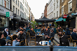 © Licensed to London News Pictures. 12/04/2021. LONDON, UK.  People enjoying food and drink in Soho where restaurants are offering al fresco dining following the UK government's coronavirus roadmap out of lockdown which allowed non-essential businesses to reopen today.  Photo credit: Stephen Chung/LNP