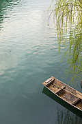 View of a single traditional wooden boat on the surface of the water in the Tuojiang River, Fenghuang, Hunan Province, China