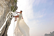 NANNING, CHINA - DECEMBER 29:  China Out - Finland Out<br /> <br /> Wedding Photos on Cliff<br />  <br /> Miss Zheng takes wedding photographs at the cliff on December 29, 2013 in Nanning, Guangxi Province of China. Zheng and her husband, surnamed Su, both love outdoor sports and they decided to have their wedding photos taken while rock climbing. <br /> ©Exclusivepix